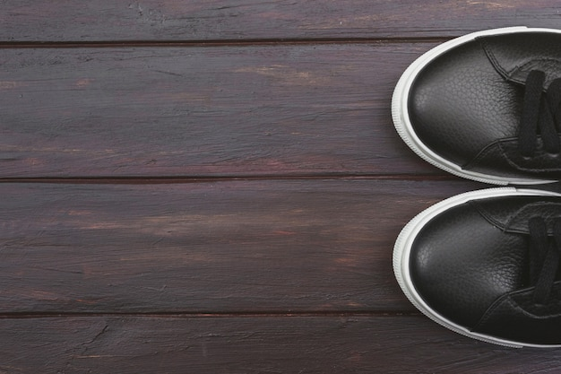 Casual black leather sneakers on wooden background