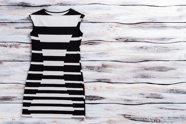 Casual black and white dress. sleeveless dress on wooden background. modern garment for ladies. merchandise at special price.