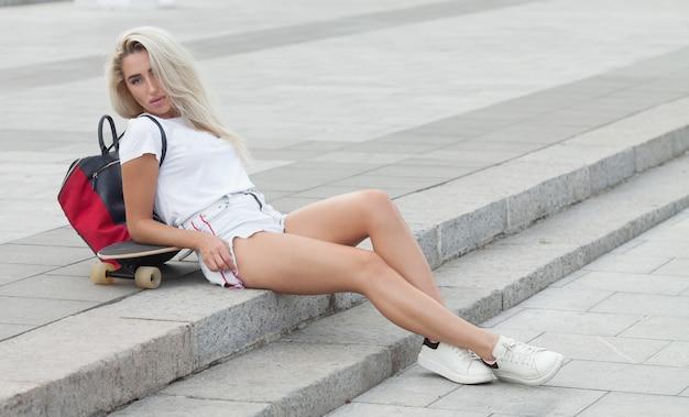 Повседневная белокурая женщина в джинсовых шортах позирует на лестнице с longboard.