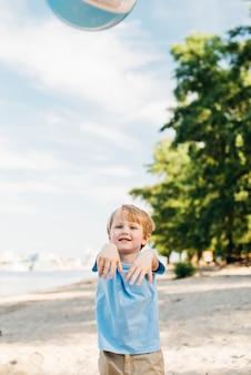 Casual boy throwing beach ball