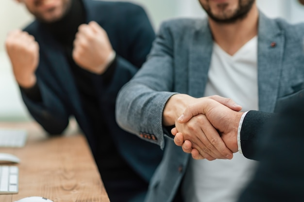 同僚と握手するカジュアルなビジネスマン