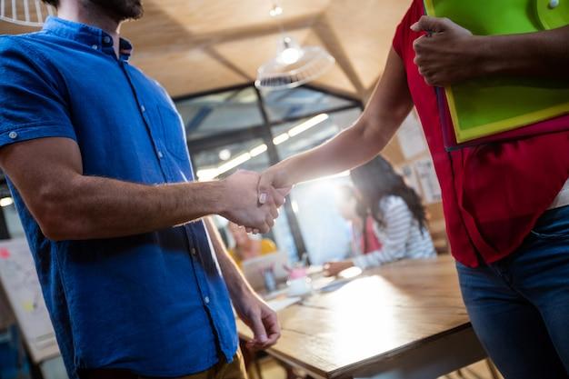 Случайные деловые люди пожимают друг другу руки