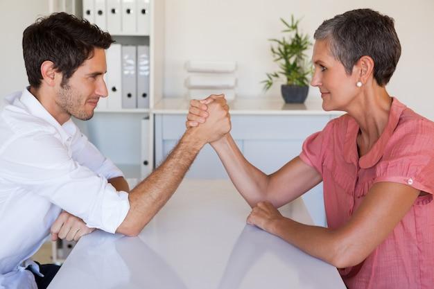 Casual business team arm wrestling at desk