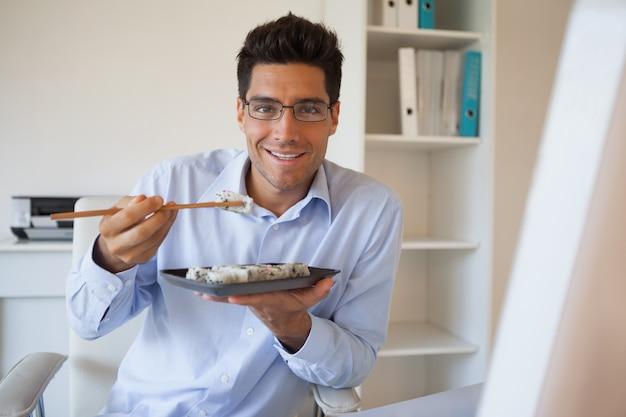 彼の机で寿司を楽しむカジュアルなビジネスマン
