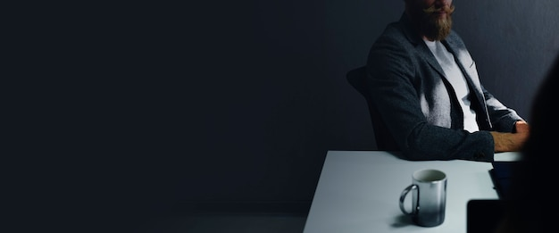 Casual businessman sitting in the dark