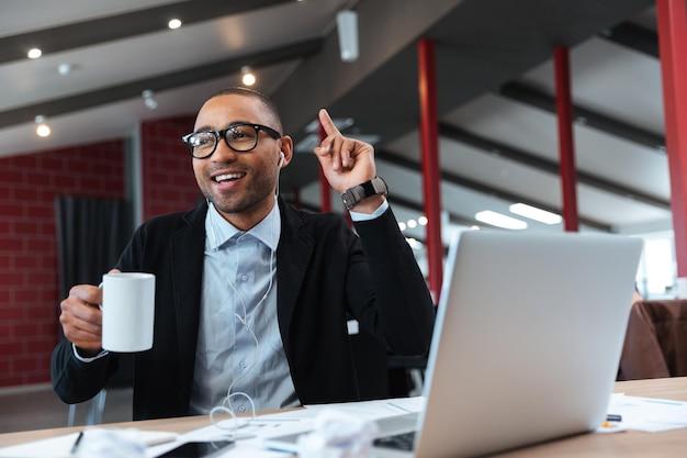 Случайный бизнесмен сидит с ноутбуком и имеет идею в офисе