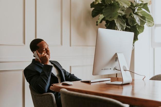 オフィスで働いている間電話で話しているカジュアルなビジネスマン