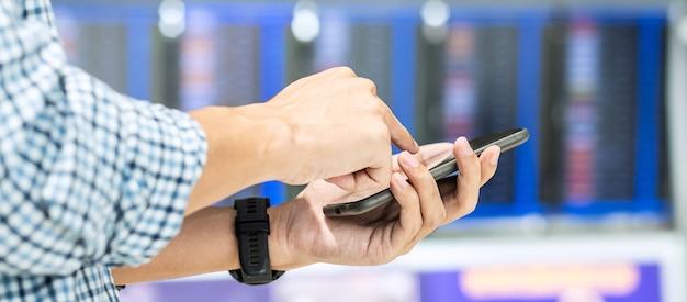 공항에서 항공편 정보 게시판에서 스마트 폰을 사용하는 캐주얼 사업가