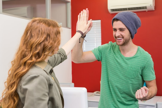 Casual businessman and woman high fiving
