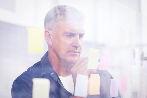 カジュアルなビジネスマンは、オフィスで壁に貼り付いた投稿を書いています