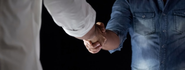 Casual businessmen making handshake during the meeting at night