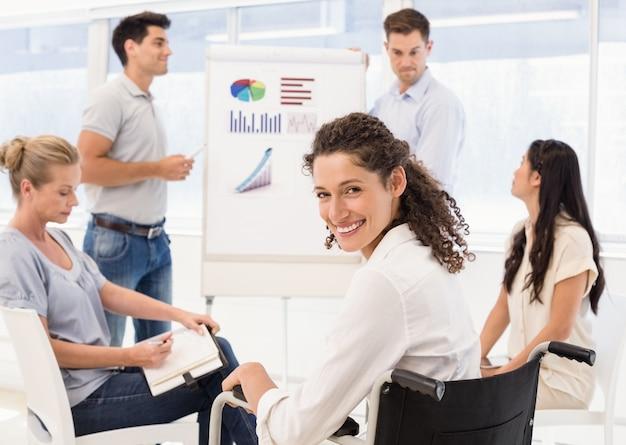 会議中にカメラで笑っている車椅子のカジュアルな実業家