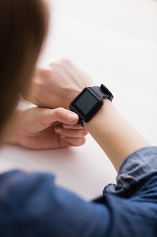 Casual businesswoman using her smart watch at her desk in office
