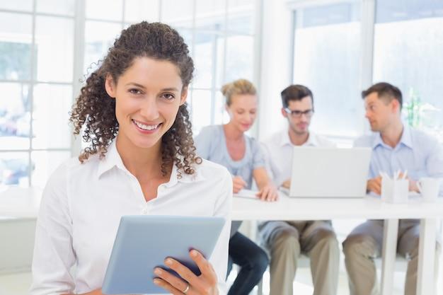 彼女の後ろにチームとタブレットを使用しているカジュアルなビジネスマン