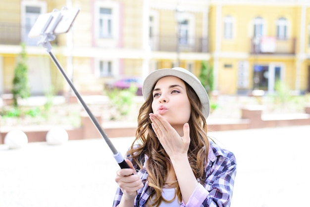 Casual cap trendy urban stylish shirt facial emotion expressing style headwear mouth outdoors concept. close up portrait of fun funny joyful joy lovely girl taking making selfie using selfie stick