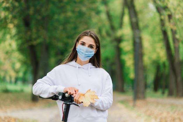 混沌としたパンデミックの間に都市公園で都市の電動スクーターに乗って保護フェイスマスクを身に着けているカジュアルな白人女性。アーバンモビリティのコンセプト。
