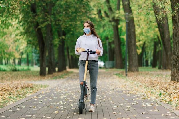 코로나 바이러스 전염병 동안 도시 공원에서 도시 전기 스쿠터를 타고 보호 얼굴 마스크를 쓰고 캐주얼 백인 여성. 도시 이동성 개념.