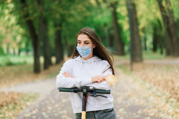 도시에서 도시 전기 스쿠터를 타고 보호 얼굴 마스크를 쓰고 캐주얼 백인 여성