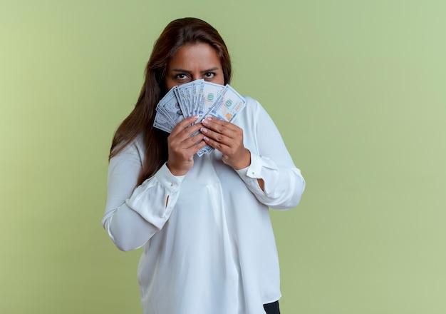 カジュアルな白人の中年女性がお金で顔を覆った