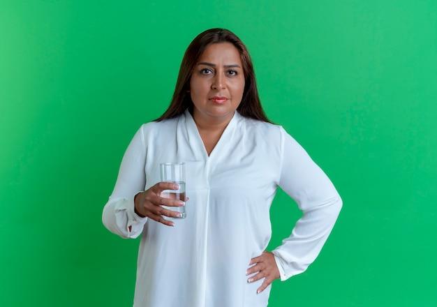 コップ一杯の水を保持し、腰に手を置くカジュアルな白人の中年女性