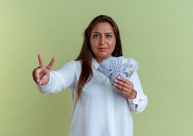 돈을 들고 평화 제스처를 보여주는 캐주얼 백인 중년 여성