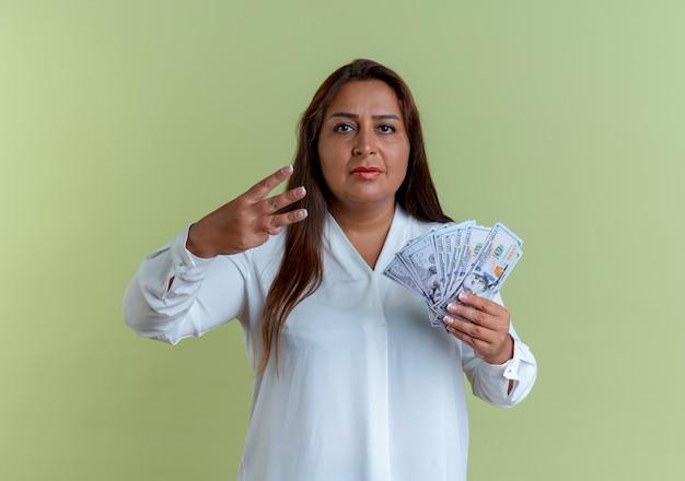 Donna di mezza età caucasica casuale che tiene soldi e che mostra tre