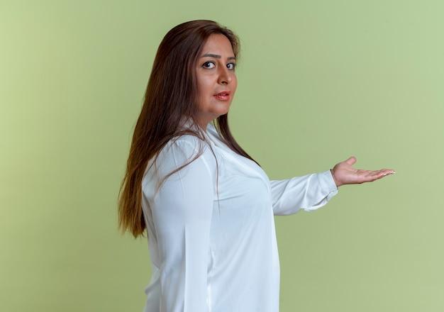 Casual indoeuropea donna di mezza età tendendo mano a lato