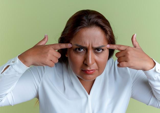 Donna di mezza età caucasica casuale che mette le dita sulla fronte