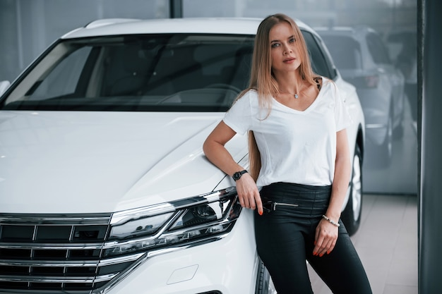 In casual clothes. girl and modern car in the salon. at daytime indoors. buying new vehicle.