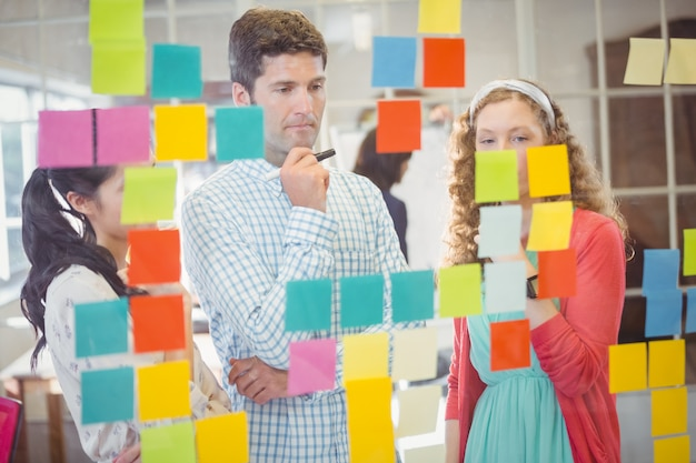 Casual colleagues looking at sticky notes on wall