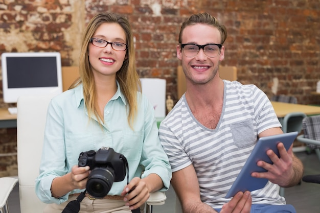 Casual colleagues with digital camera and tablet in office