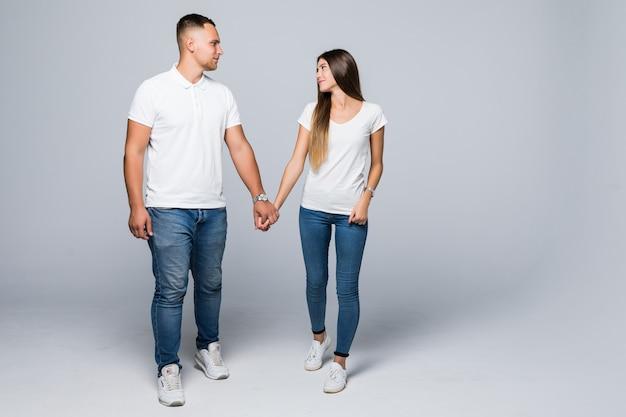 Случайная пара идет к камере, глядя друг на друга, изолированную на белой стене