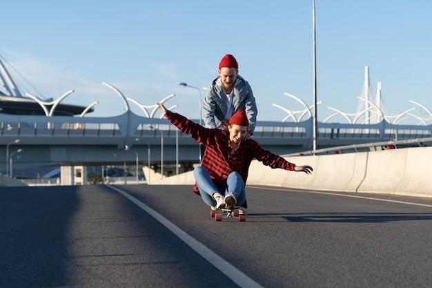 Casual couple on longboard man teaching girl to balance on skateboard push her back down empty road