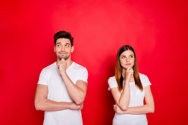 赤い壁に向かってポーズをとるカジュアルなカップル