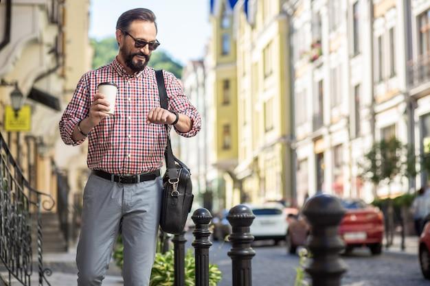 Случайные дни. позитивный взрослый мужчина улыбается во время прогулки по улице