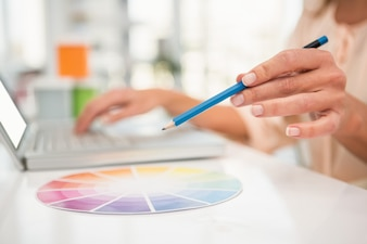 Casual designer working with laptop and colour chart in the office