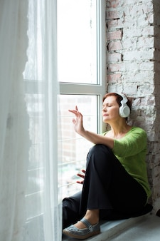 Casual dressed senior woman listening music