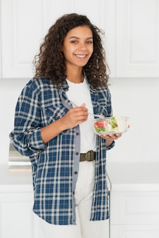Casual dressed woman eating salad