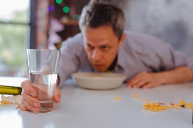 カジュアルな飲酒。テーブルの上に立っているガラスに注ぐ冷たい澄んだ水の選択的な焦点