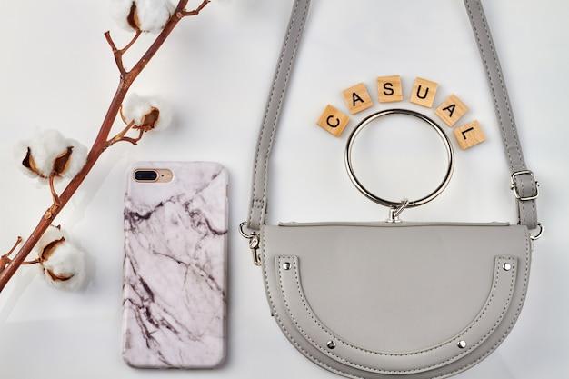 カジュアルなファッションコンセプト。女性のためのバイオレットポーチと白い背景の上の栄光の携帯電話。