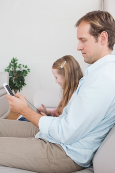Casual father and daughter using tablet and smartphone on the couch