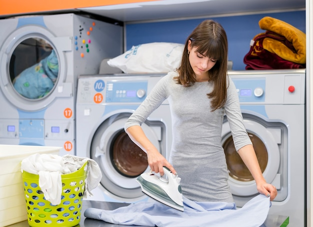 Casual female ironing clothes medium shot