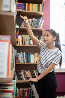 Повседневная девушка-подросток стоит у книжной полки в библиотеке колледжа и берет книгу, собираясь подготовиться к уроку