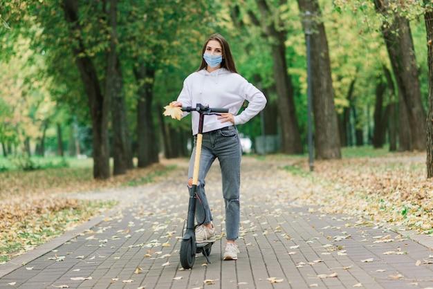 都市の電動スクーターに乗って保護フェイスマスクを身に着けているカジュアルな女性