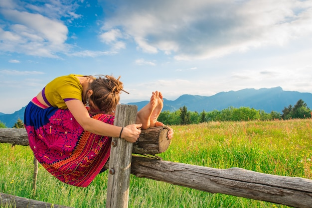 Casual girl relaxes doing stretching and yoga alone in the mountains over a fence in a beautiful spring meadow.