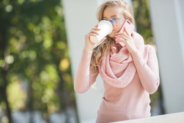 公園で携帯電話で話しているカジュアルな女の子。魅力的な若い女性は彼女の友達とモバイルでチャット。