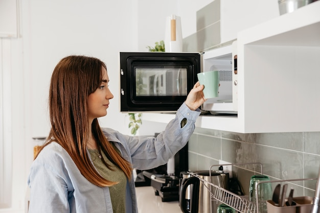 Casual girl using microwave to heat cup