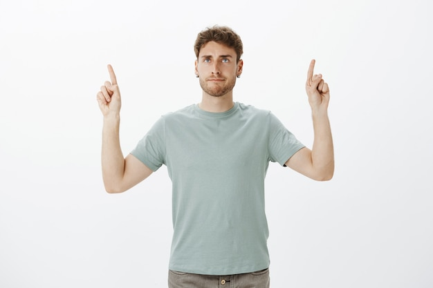 Casual good-looking male coworker in t-shirt, raising index fingers and pointing up while making indifferent annoyed grimace