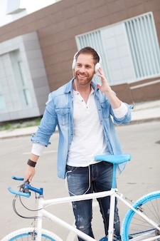 Casual guy next to a vintage bicycle listening music