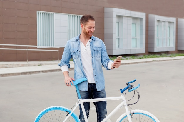 Casual guy next to a vintage bicycle with the mobile